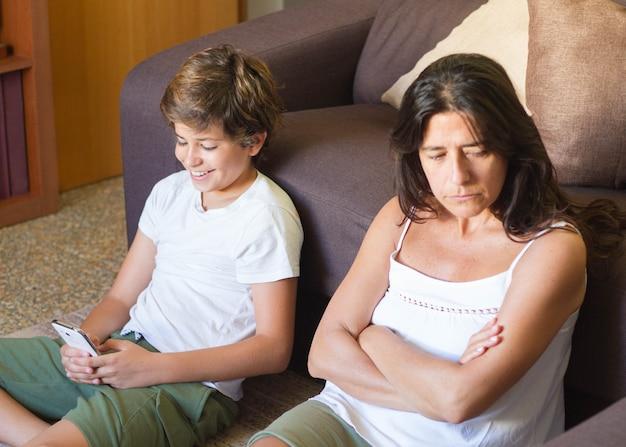 Een boze moeder terwijl haar tienerzoon sociale netwerksites misbruikt