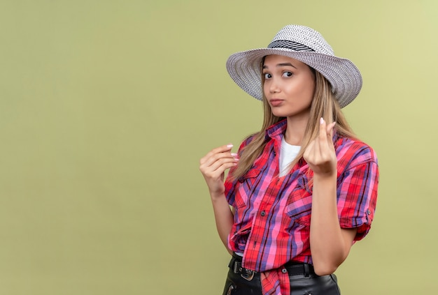 Een boze mooie jonge vrouw in een gecontroleerd overhemd in hoed die geen geldgebaar met hand toont