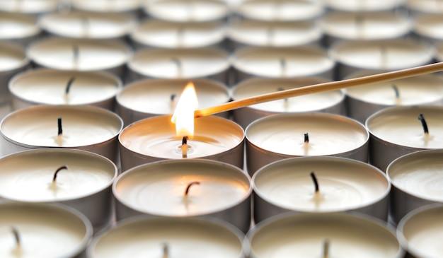 Een brandende kaars en veel gedoofde kaarsen