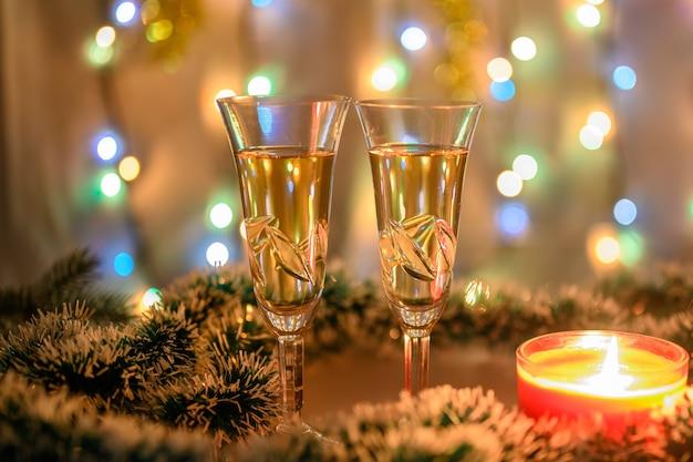 Een brandende kaars, glazen mousserende wijn tegen de achtergrond van een sprankelende slinger in koude kleuren.