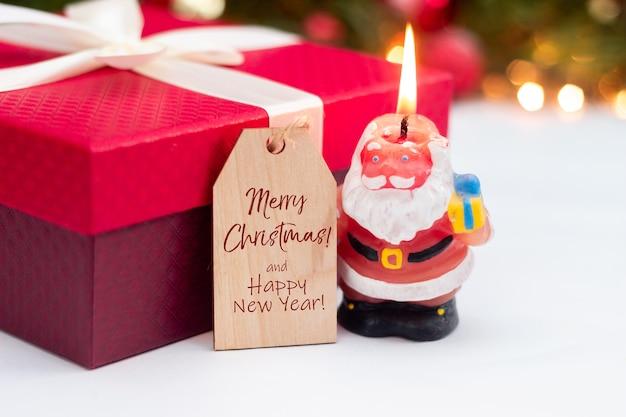 Een brandende kaars in de vorm van de kerstman rode geschenkdoos houten notitie kerstversiering