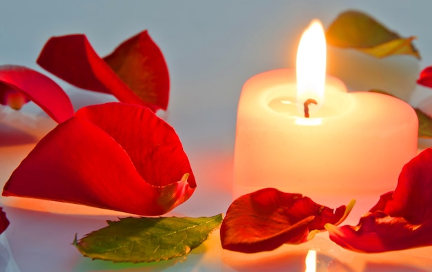 Een brandende kaars in rozenblaadjes in hartvorm