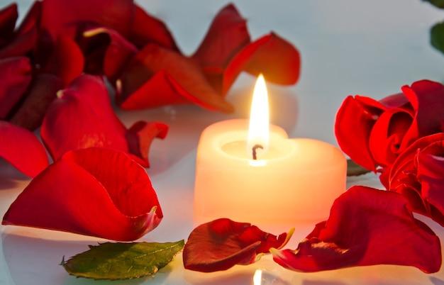 Een brandende kaars in rozenblaadjes