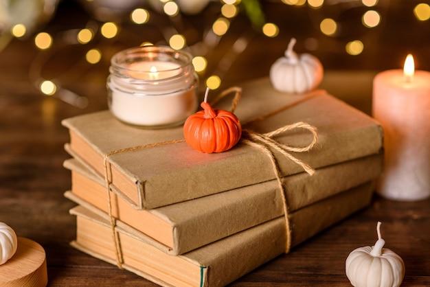 Een brandende kaars op een houten tafel voor een boek in een halfstok. aan het leren. de bijbel bestuderen