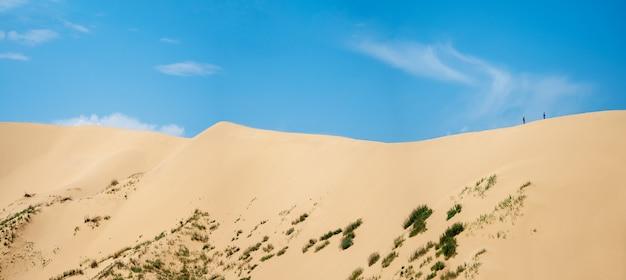 Een breed panorama van een groot duin met een klein silhouet van mensen die erop lopen tegen de blauwe lucht.