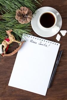 Een brief aan de kerstman op tafel met thee en kerstversieringen