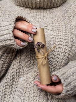 Een brief versierd met een bloem van oregano in de handen van een meisje. een meisje in een wollen trui houdt een brief van kraftpapier vast. pre-vakantiesfeer