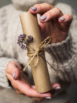 Een brief versierd met een bloem van oregano in de handen van een meisje