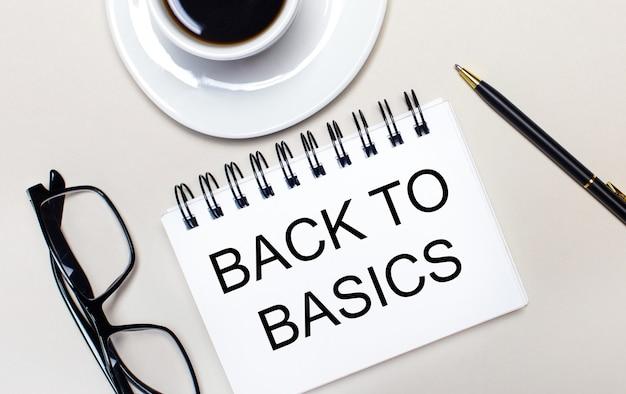 Een bril, een witte kop koffie, een wit notitieboekje met de woorden back to basics en een balpen liggen op een lichte achtergrond. plat leggen. uitzicht van boven.