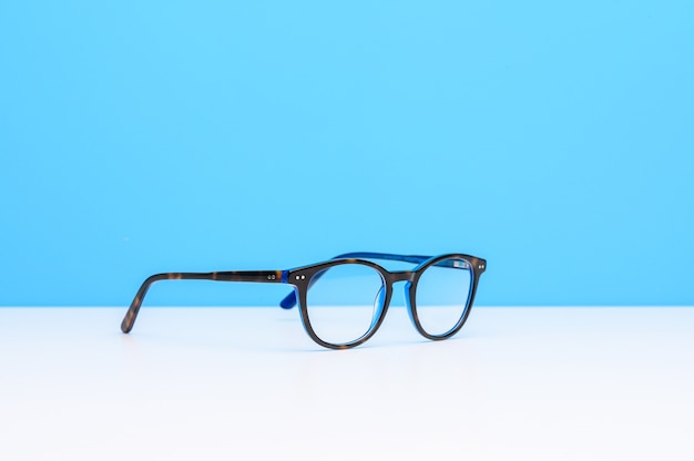Een bril op een wit oppervlak met een blauwe achtergrond