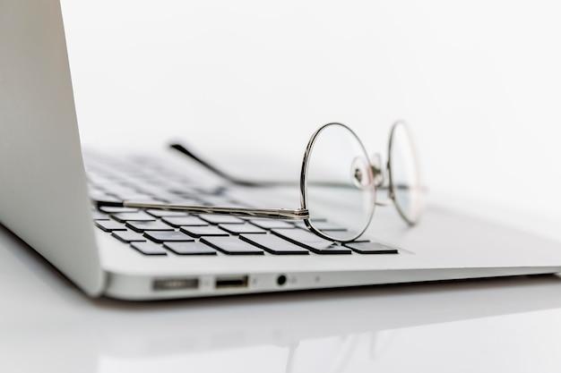 Een bril staat op de laptop. . ruimte voor tekst.