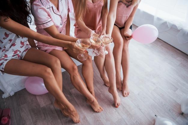 Een bril vasthouden. alleen benen en lichamen. vrijgezellin vieren in witte slaapkamer. meisjes met champagne