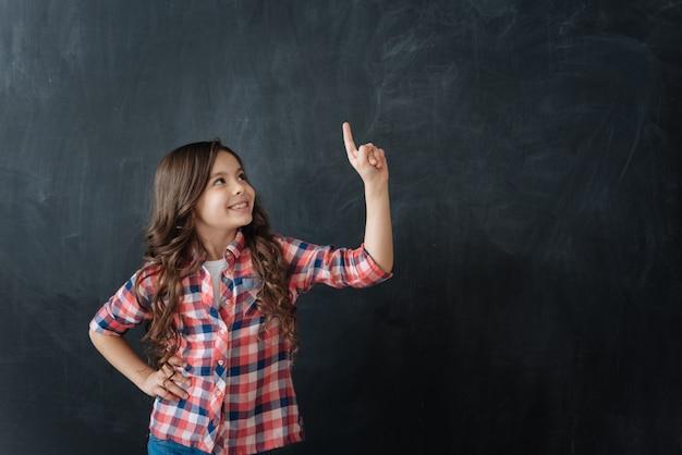Een briljant idee hebben. creatief inventief optimistisch meisje dat tegen bord staat en geniet van denkbeeldige tekening terwijl ze geluk uitdrukt