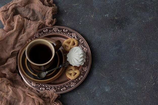 Een bronzen bord een kopje koffie, pretzels en marshmallows