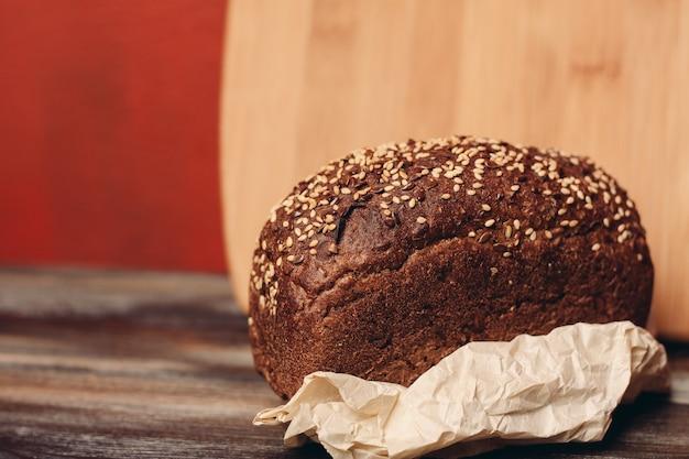 Een brood van roggebrood op papieren onderzetters en een bord op de achtergrond van een houten tafel