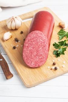 Een brood van salami servelat worst op een snijplank met peterselie en kruiden en knoflook.