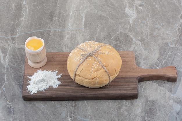 Een brood van wit brood met dooier en bloem op een houten bord
