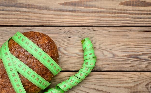 Een brood van zemelenbrood omwikkeld met een liniaal op een houten tafel. het concept van gezond eten, afvallen. bovenaanzicht.