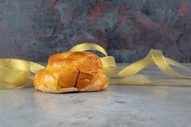 Een broodje en gele linten op marmer