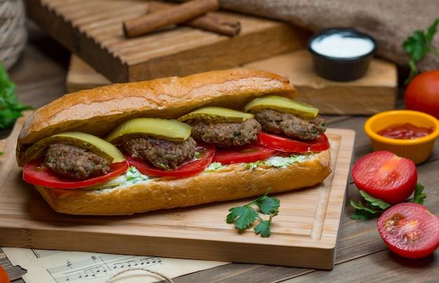 Een broodje gevuld met gehaktballetjes, groene paprika, plakjes tomaat en sandwich-dipsaus