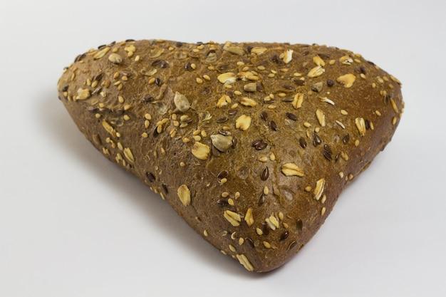 Een broodje in de vorm van een driehoek bestrooid met zonnebloempitten en sesamzaadjes. witte achtergrond