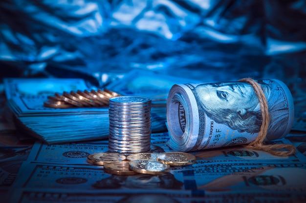 Een broodje van dollars met muntstukken op de achtergrond van verspreide honderd dollarsrekeningen in blauw licht.