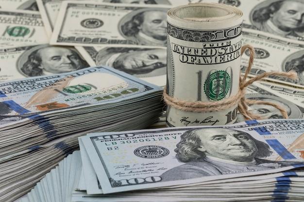 Een broodje van honderd dollarsrekeningen bond met een kabel tegen de achtergrond van verspreide dollars.