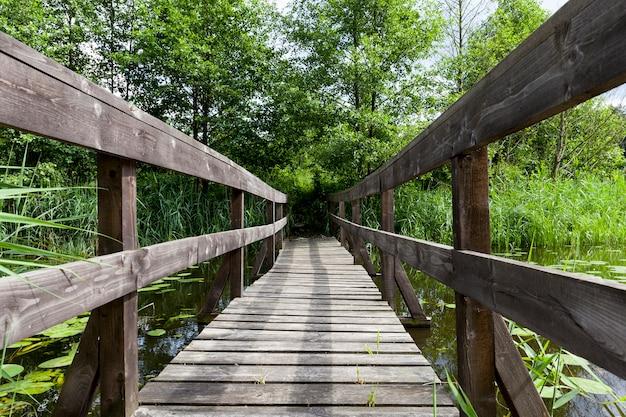 Een brug tussen kleine eilanden op het meer, oude houten brug gebouwd op het meer