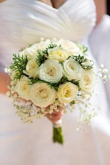 Een bruid die een close-up van het huwelijksboeket houdt