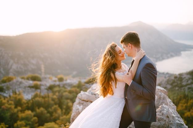 Een bruid en een bruidegom knuffelen elkaar op de berg lovcen, een panoramisch uitzicht over de baai van kotor