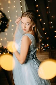 Een bruid in een blauwe avondjurk staat met haar ogen dicht en droomt