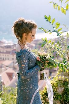 Een bruid in een blauwe jurk staat met een boeket in haar handen achter zich en opent een uitzicht over de oude stad