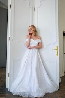 Een bruid in een chique trouwjurk staat bij de deur en kijkt bedachtzaam opzij