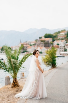 Een bruid in een delicate jurk en een sluier staat op de pier bij het oude centrum van perast
