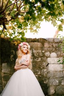 Een bruid in een delicate krans staat bij een bakstenen muur onder een vijgenboom met haar armen over haar borst gevouwen