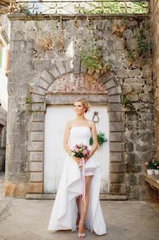Een bruid in een elegante jurk met een boeket in haar handen staat voor de witte deuren van een mooie oude vrouw
