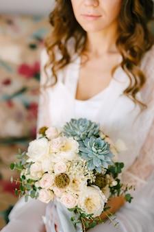 Een bruid in een kanten gewaad zit op een bank in een hotelkamer en heeft een bruidsboeket in haar handen