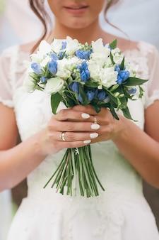 Een bruid in een mooie jurk met een trein met een boeket bloemen en groen