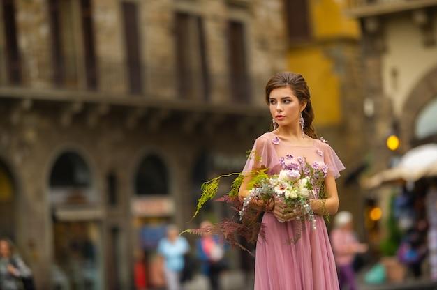 Een bruid in een roze jurk met een boeket staat in het centrum van de oude stad van florence in italië.