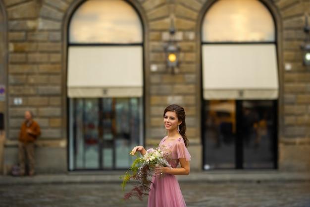Een bruid in een roze jurk met een boeket staat in het centrum van de oude stad van florence in italië
