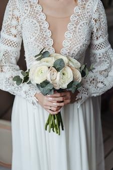 Een bruid in een trouwjurk in boho-stijl houdt een boeket delicate bloemen vast.
