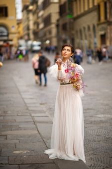 Een bruid in een trouwjurk met een venetiaans masker in haar handen in florence, italië.