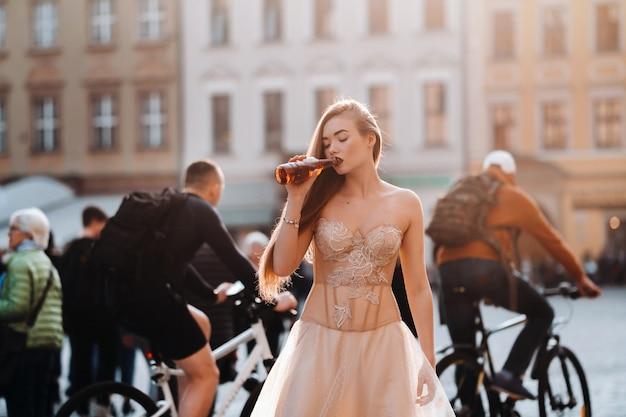 Een bruid in een trouwjurk met lang haar en een drinkfles in de oude binnenstad van wroclaw. bruiloft fotoshoot in het centrum van een oude poolse stad. wroclaw, polen.