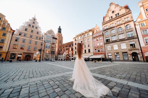 Een bruid in een trouwjurk met lang haar in het oude centrum van wroclaw. bruiloft fotoshoot in het centrum van een oude stad in poland.wroclaw, polen.
