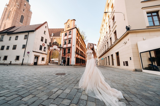 Een bruid in een trouwjurk met lang haar in het oude centrum van wroclaw