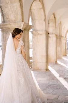 Een bruid in een witte jurk en met een lange sluier, achteraanzicht