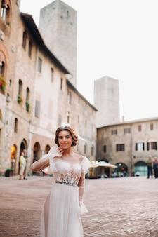 Een bruid in een witte jurk in het oude centrum van san gimignano.