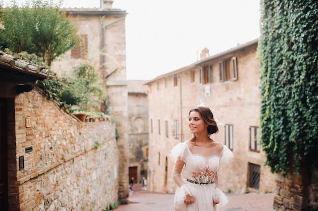 Een bruid in een witte jurk in het oude centrum van san gimignano