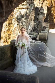 Een bruid in een witte jurk met een boeket bloemen