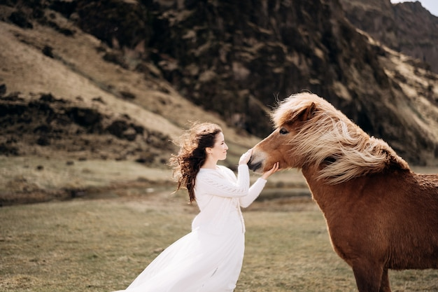 Een bruid in een witte jurk streelt een paardenneus, haar en manen ontwikkelen zich in de windbestemming ijsland